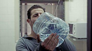 Un uomo assetato beve acqua da un bottiglione. I dolci fanno venire sete!
