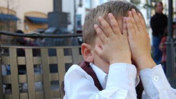 Un bambino imbarazzato si nascondo il viso con le mani
