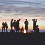 Gruppo di giovani amici attorno un falò per Ferragosto