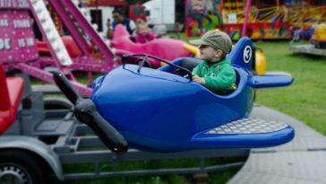 Bambino su giostra guida aereo