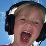 Bambina con cuffie che ascolta la sua voce