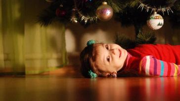 Una dolce bambina sotto l'albero di natale chissà quando si addobba