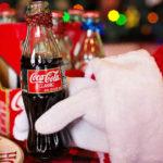 Babbo Natale tiene in mano una bottiglia piccola di coca cola