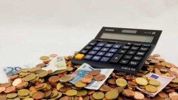 Una calcolatrice su una montagna di euro, sia monete che banconote, pronta a calcolare la liquidazione del TFR