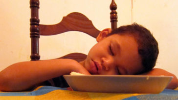 Bambino si addormenta al tavolo dopo aver mangiato un pasto abbondante che gli ha causato sonno