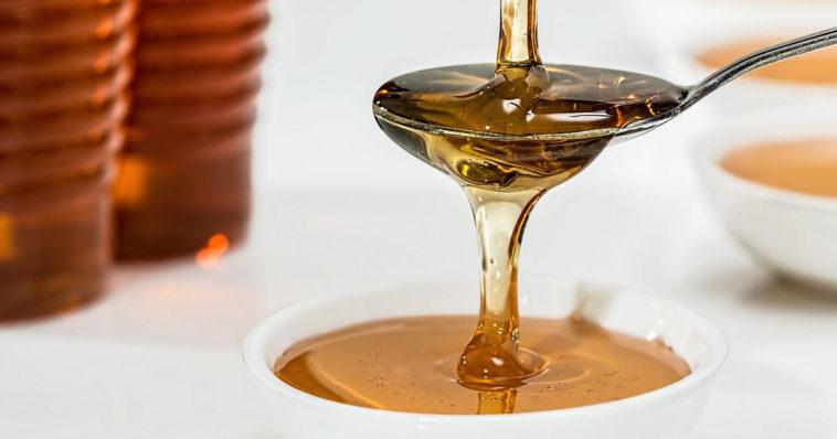 Miele versato con cucchiaino in tazza con latte