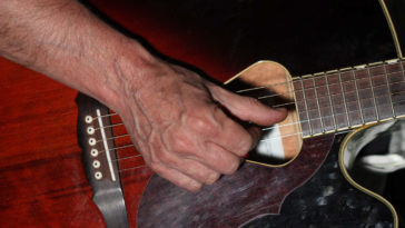 Chitarrista con mano con delle vene blu molto visibili