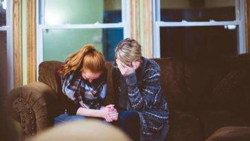 Donne che piangono su un divano consolandosi a vicenda