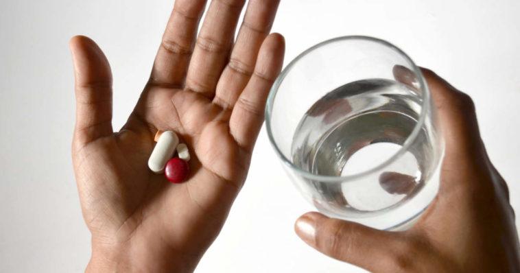 Un uomo ingoia una medicina in pillola con un bicchiere d'acqua ma ha paura di soffocare