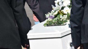 Funerale con persone che trasportano una bara bianca con dei fiori per dire condoglianze