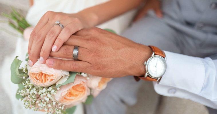 sposi che si tengono per mano tenendo bouquet e orologio