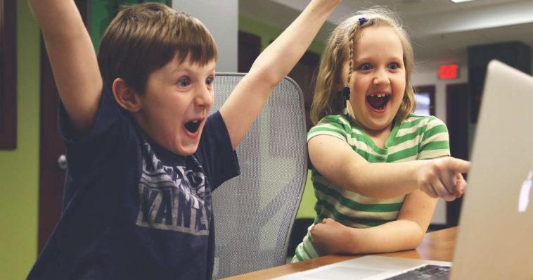 Dei bambini felici si divertono giocando al computer e il loro tempo è volato