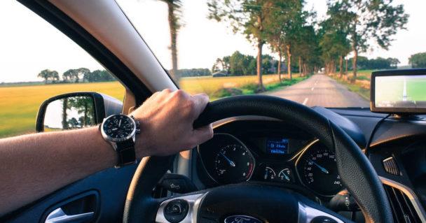 Uomo con orologio al polso guida un auto sul viaggio di ritorno che sembra più breve di quello dell'andata