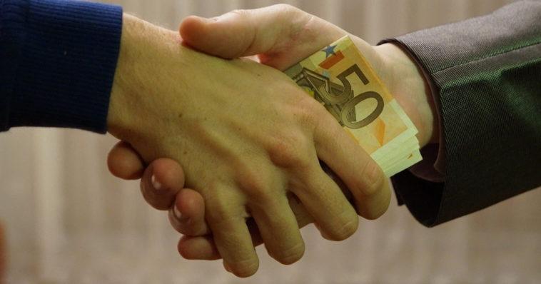 Due mani che si stringono, scambiandosi delle banconote