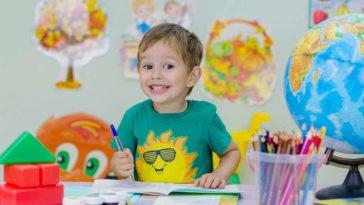 Bambino seduto al banco sorride felice di imparare nuove lingue straniere