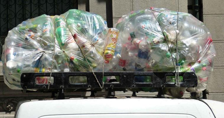 Un furgoncino bianco trasporta sul tetto dei sacchi pieni di bottiglie di plastica da riciclare
