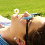 Una ragazza prende il sole stesa su un prato